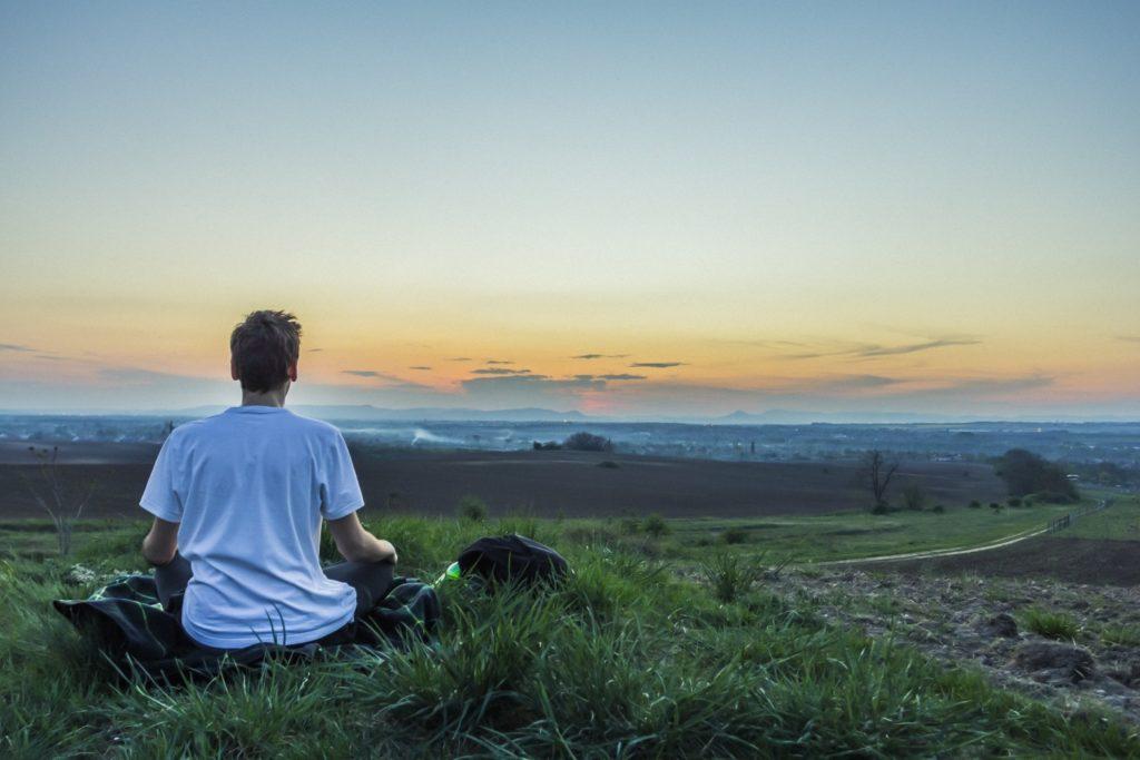 homme de dos en tailleur en méditation