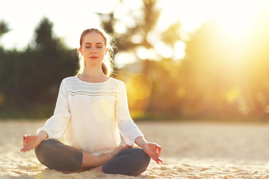 femme les yeux fermés assise en tailleur en méditation